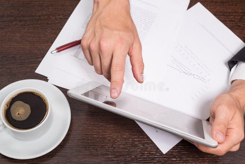 Den lyckade affärsmannen använder internet på hans minnestavlaPC, i arbetsplatsen är dokument med scheman och en kopp kaffe royaltyfri bild