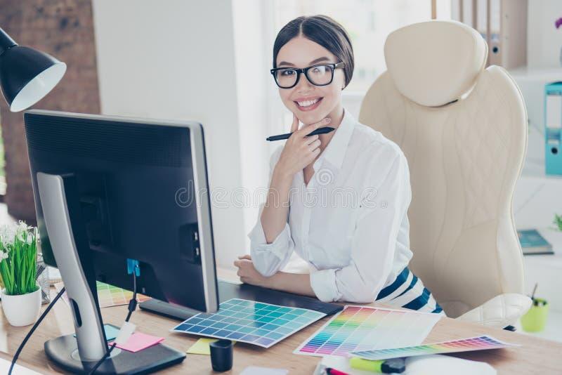 Den lyckade attraktiva affärsdamformgivaren sitter på hennes w arkivbild