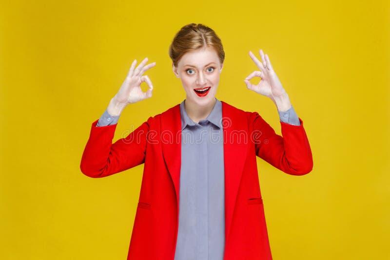 Den lyckade brunnen klädde den röda head affärskvinnan som visar det ok tecknet royaltyfri foto
