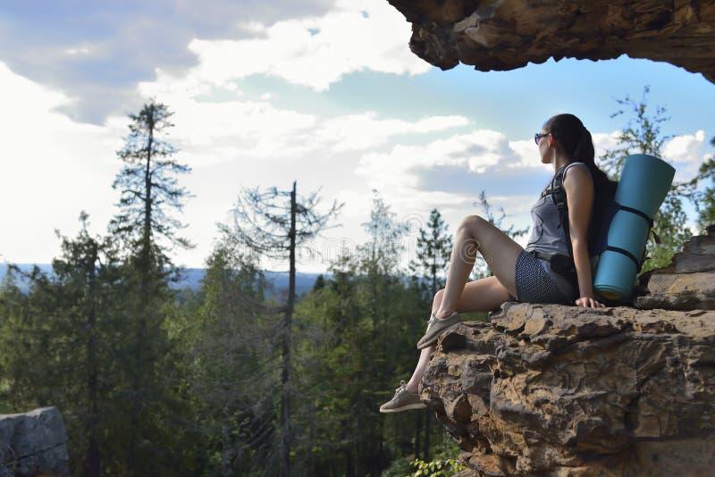 Den lyckade kvinnafotvandraren tycker om sikten på bästa se för berg långt borta fotografering för bildbyråer