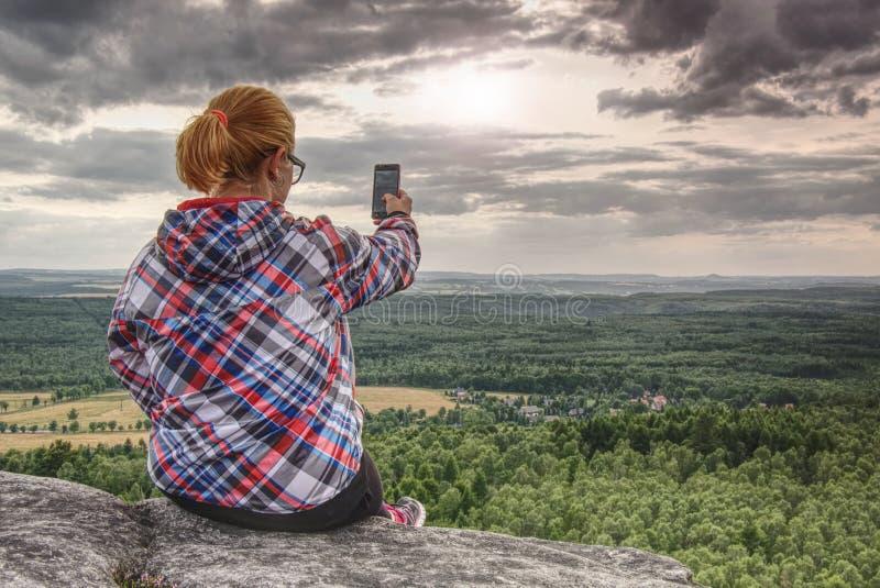 Den lyckade kvinnliga fotvandraren tar fotoet på kanten royaltyfri foto