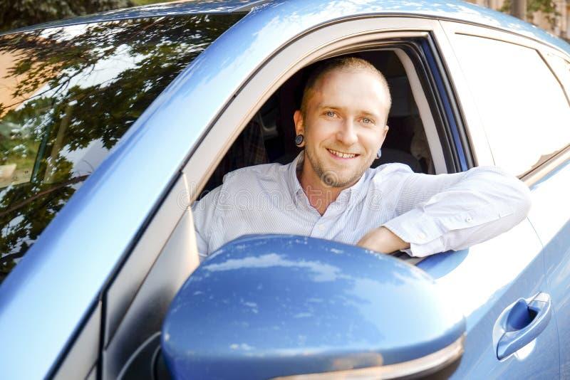 Den lyckade lyckliga unga mannen och hans bil i mjuk solnedgång tänder på urbanistic bakgrund Affärsman med medlet på vägrenen arkivbilder