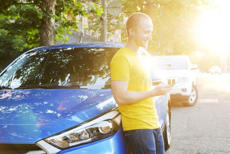 Den lyckade lyckliga unga mannen och hans bil i mjuk solnedgång tänder på urbanistic bakgrund Affärsman med medlet på vägrenen royaltyfri bild