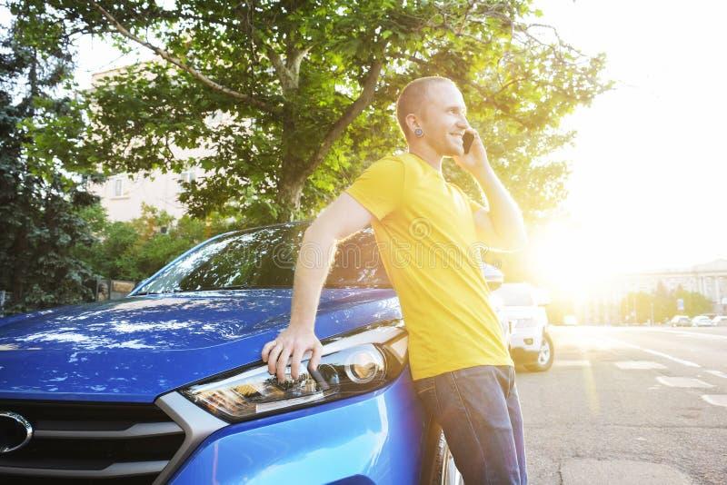 Den lyckade lyckliga unga mannen och hans bil i mjuk solnedgång tänder på urbanistic bakgrund Affärsman med medlet på vägrenen royaltyfri fotografi