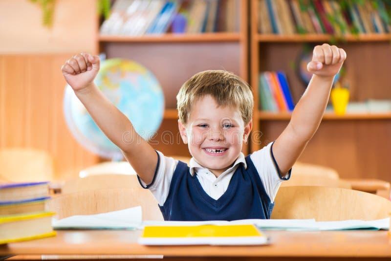 Den lyckade skolpojken med händer up sammanträde på skrivbordet royaltyfri fotografi