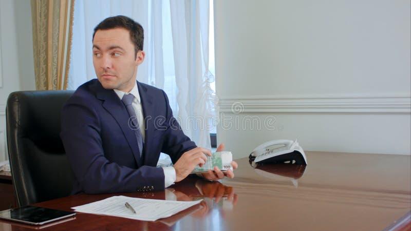 Den lyckade unga affärsmannen räknar euroräkningar som talar med kollegan i kontoret royaltyfri fotografi