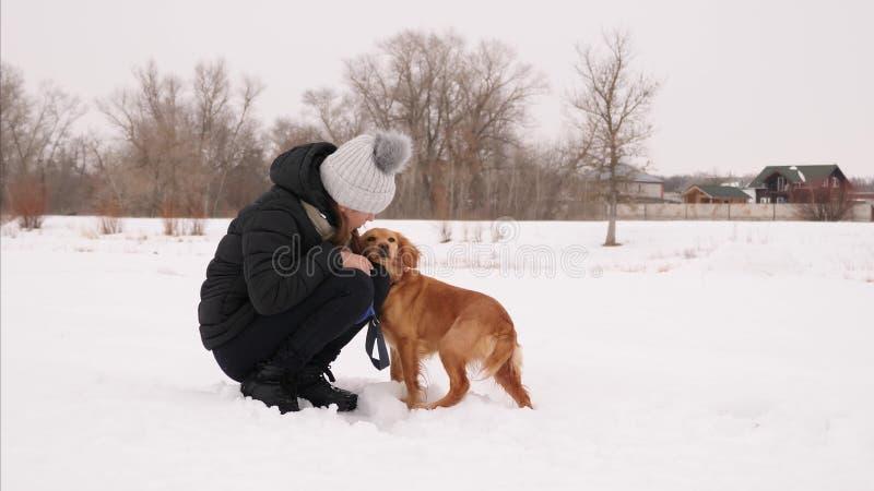 Den lyckliga ägaren som spelar med hans hund i snö, parkerar och att le arkivbild