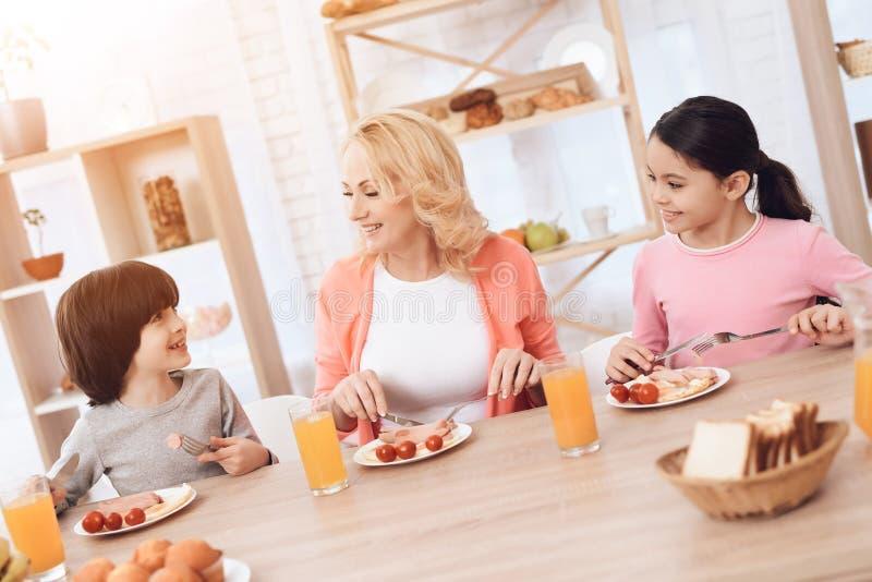 Den lyckliga äldre kvinnan äter middag med hennes barnbarn på matställetabellen i kök arkivfoton