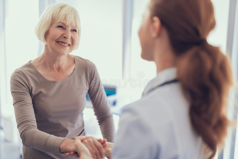 Den lyckliga åldriga kvinnan tackar doktorn för omsorg royaltyfria foton