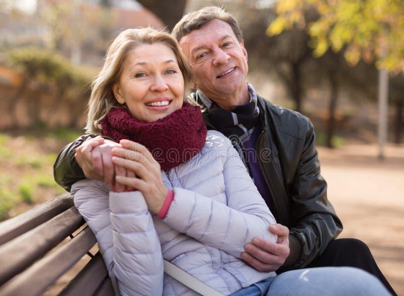 Den lyckliga åldringen kopplar ihop på en bänk i parkera i höstdag royaltyfria foton