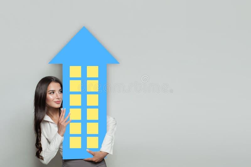 Den lyckliga affärskvinnan intecknar mäklaren eller fastighetsmäklare med huset på bakgrund med kopieringsutrymme arkivbild