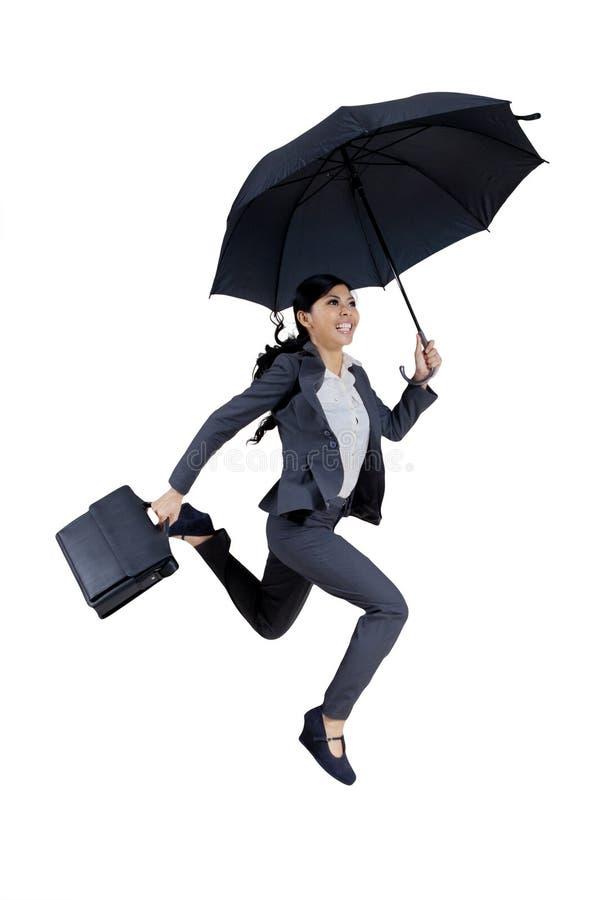 Den lyckliga affärskvinnan rymmer paraplyet på studio royaltyfria foton