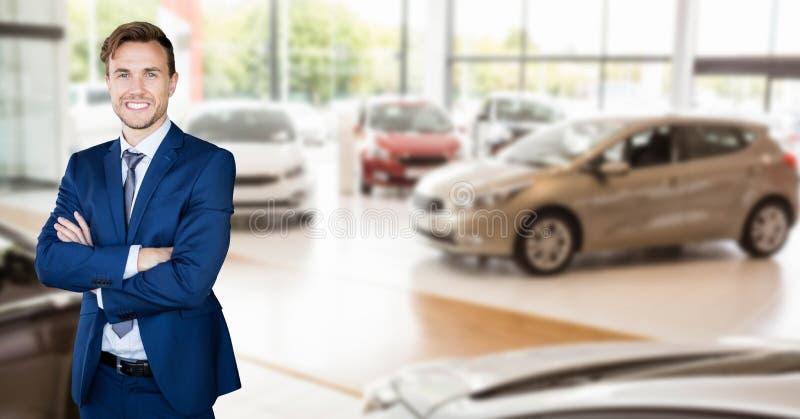 Den lyckliga affärsmannen med armar korsade anseende i bilvisningslokal royaltyfri foto
