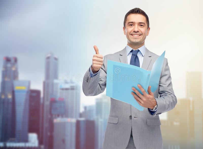 Den lyckliga affärsmannen med mappvisning tummar upp arkivfoto