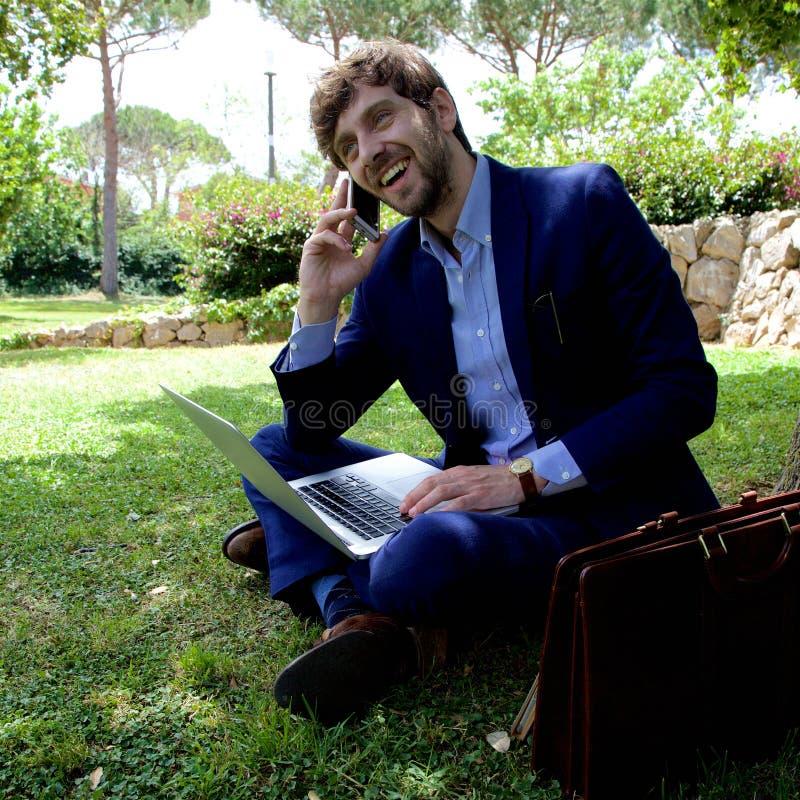Den lyckliga affärsmannen på telefonen parkerar in att skratta sned bollskottet royaltyfria foton