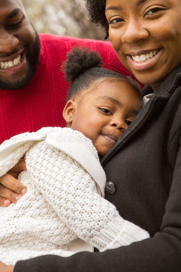 Den lyckliga afrikansk amerikanfamiljen med deras behandla som ett barn arkivfoton
