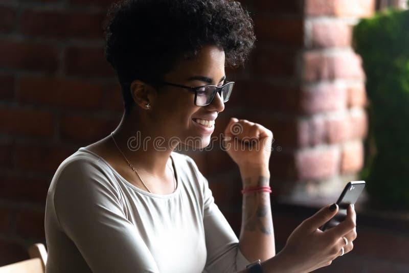 Den lyckliga afrikansk amerikankvinnan som använder telefonen, firar goda nyheter arkivfoto