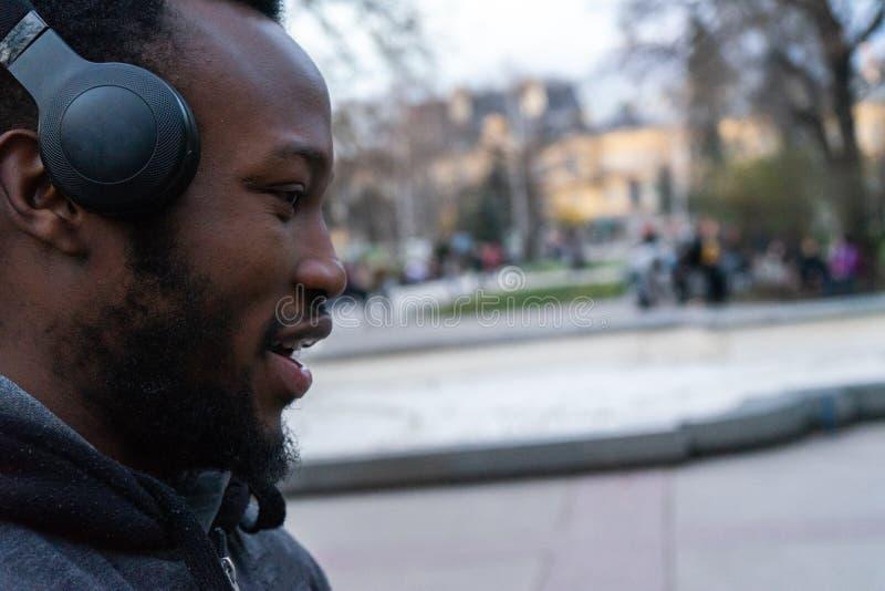 Den lyckliga afrikanska unga grabben med ett skägg och hörlurar i parkerar royaltyfri bild