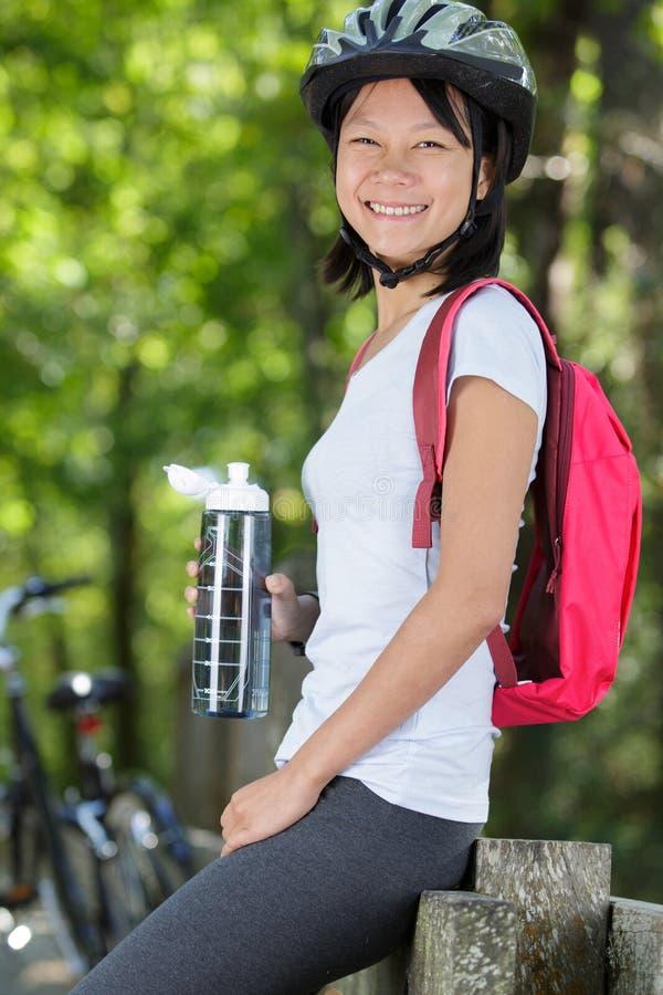 Den lyckliga aktiva flickan står med cykeln royaltyfria bilder
