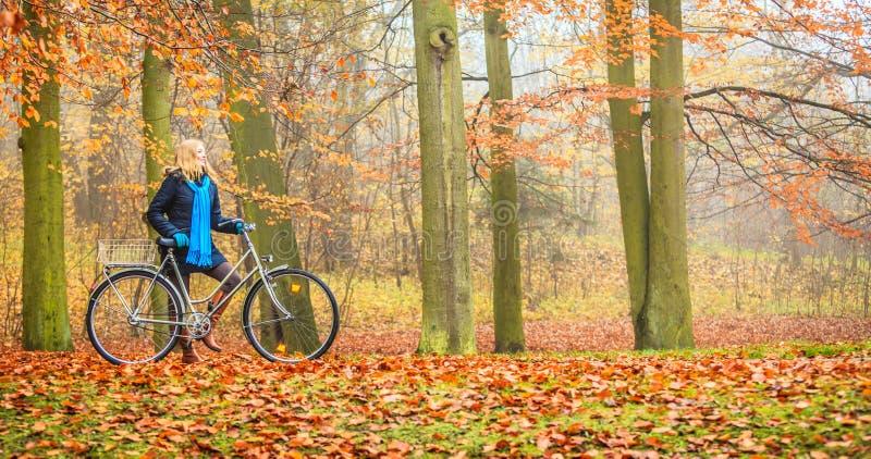 Den lyckliga aktiva kvinnaridningcykeln i höst parkerar fotografering för bildbyråer