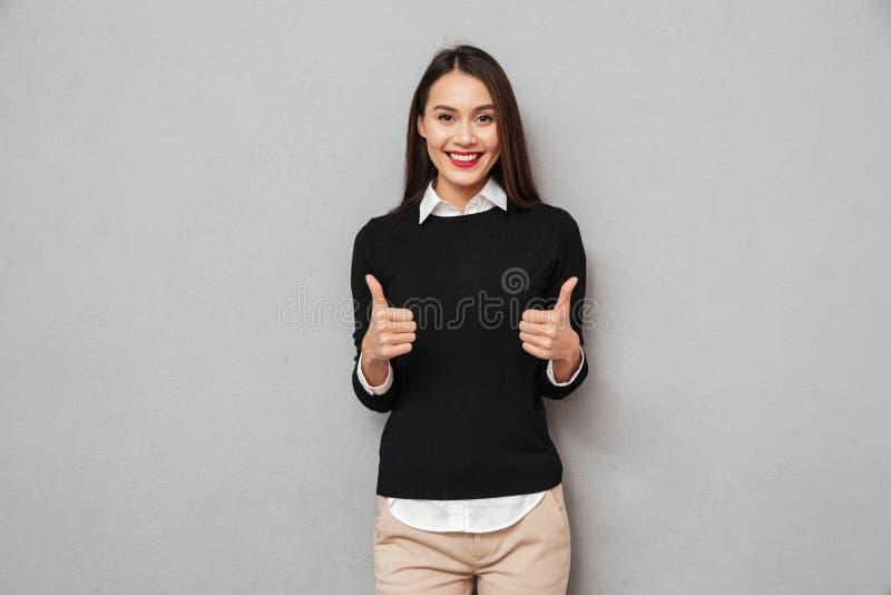 Den lyckliga asiatiska affärskvinnan i affär beklär upp visningtummar arkivfoton