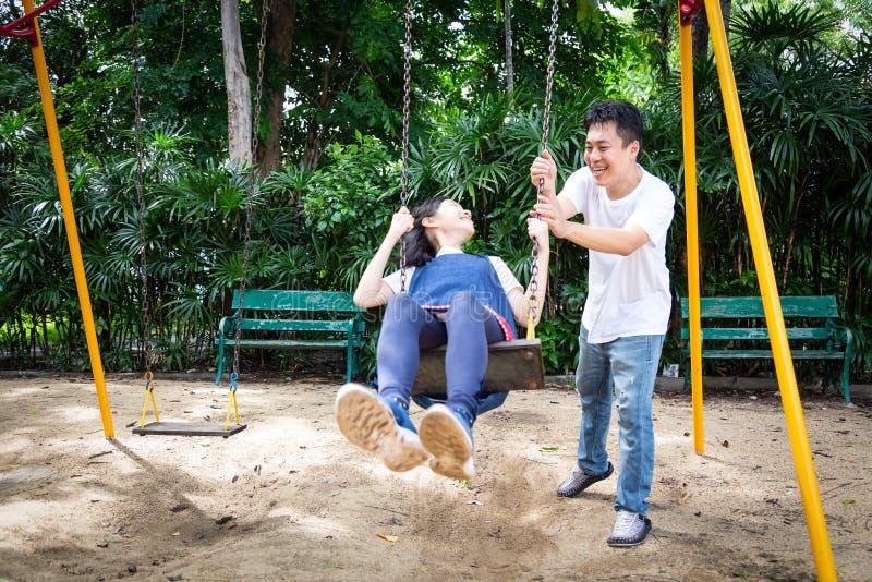 Den lyckliga asiatiska flickan för det lilla barnet som har gyckel, tycker om, skämtsamt och att spela på gungan, den härliga dot royaltyfri foto