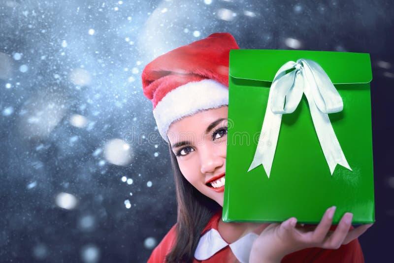 Den lyckliga asiatiska flickan med Santa Claus beklär den hållande julgåvan royaltyfri foto