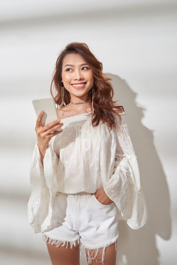 Den lyckliga asiatiska kvinnan i moderiktig kl?der som rymmer smartphonen och, jublar, medan se kameran ?ver vit bakgrund arkivbild