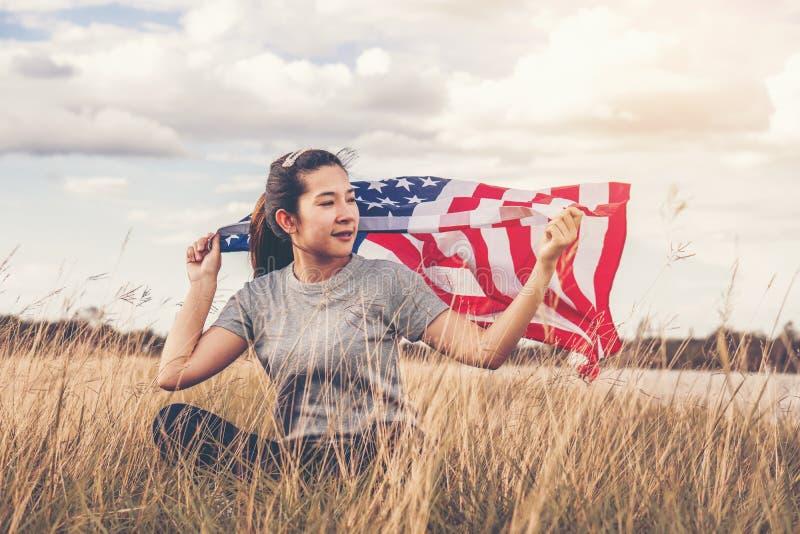 Den lyckliga asiatiska kvinnan med amerikanska flaggan USA firar 4th Juli royaltyfria bilder