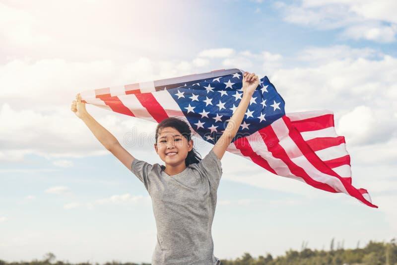 Den lyckliga asiatiska lilla flickan med amerikanska flaggan USA firar 4th Juli arkivbilder