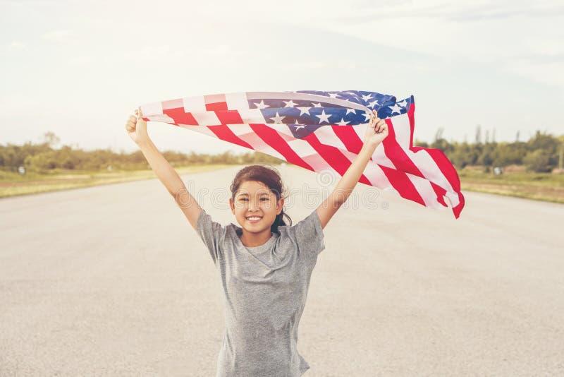 Den lyckliga asiatiska lilla flickan med amerikanska flaggan USA firar 4th Juli fotografering för bildbyråer