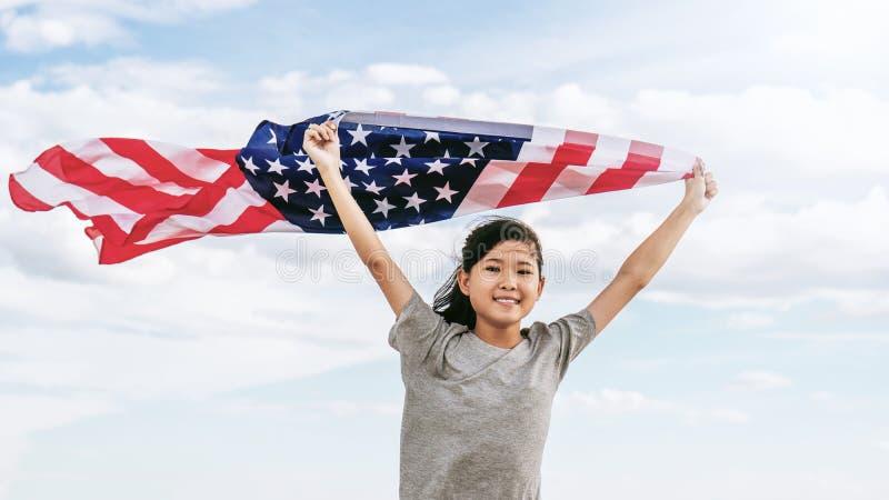 Den lyckliga asiatiska lilla flickan med amerikanska flaggan USA firar 4th Juli royaltyfri foto
