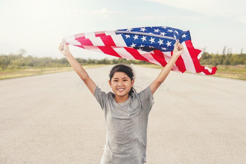 Den lyckliga asiatiska lilla flickan med amerikanska flaggan USA firar 4th Juli arkivbild