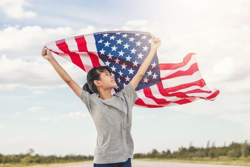 Den lyckliga asiatiska lilla flickan med amerikanska flaggan USA firar 4th Juli royaltyfri bild