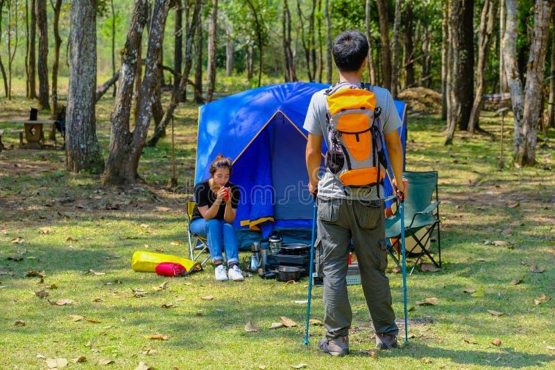 Den lyckliga asiatiska man- och kvinnaryggsäcken parkerar in, och skogbakgrund kopplar av tid på feriebegreppslopp arkivbilder