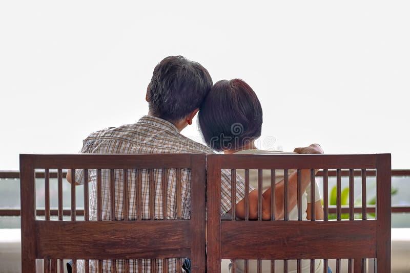 Den lyckliga asiatiska mitt åldrades ett par på bänk arkivfoto