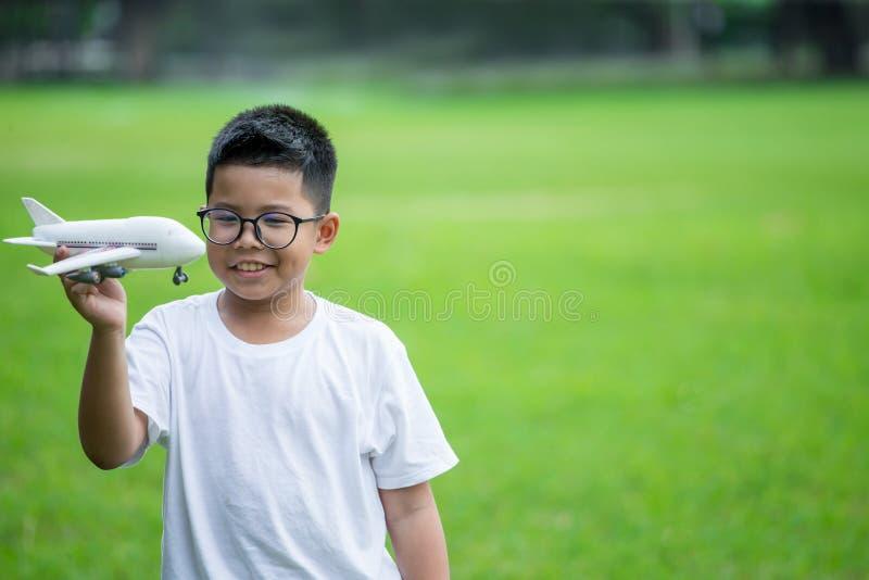 Den lyckliga asiatiska pojken som spelar med det plast- flygplanet f?r leksaken parkerar in, utomhus ungedr?mmar av resan royaltyfri foto