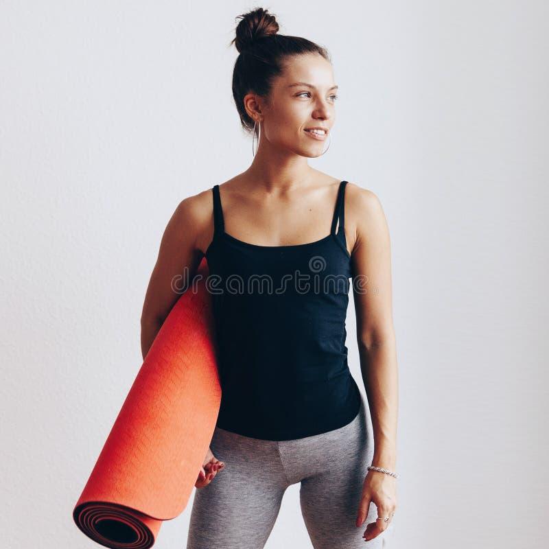Den lyckliga attraktiva unga kvinnan rymmer i yoga eller kondition för händer som röd är matta, når han har utarbetat hemma i var royaltyfri foto