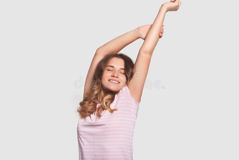 Den lyckliga avkopplade Caucasian kvinnan sträcker, når han har väckt och att vara i bra lynne som, såg angenäma drömmar, iklädd  royaltyfri foto