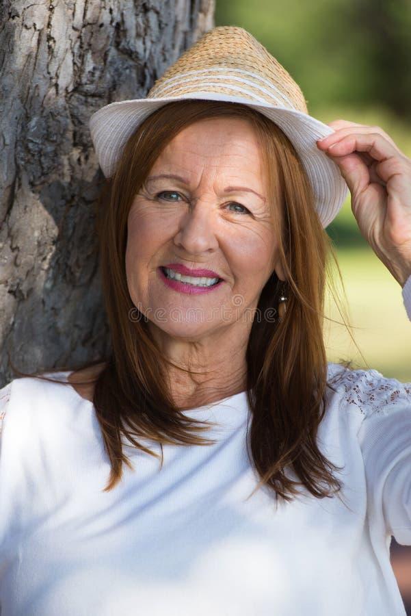 Den lyckliga avkopplade kvinnan med hatten parkerar in utanför arkivbild
