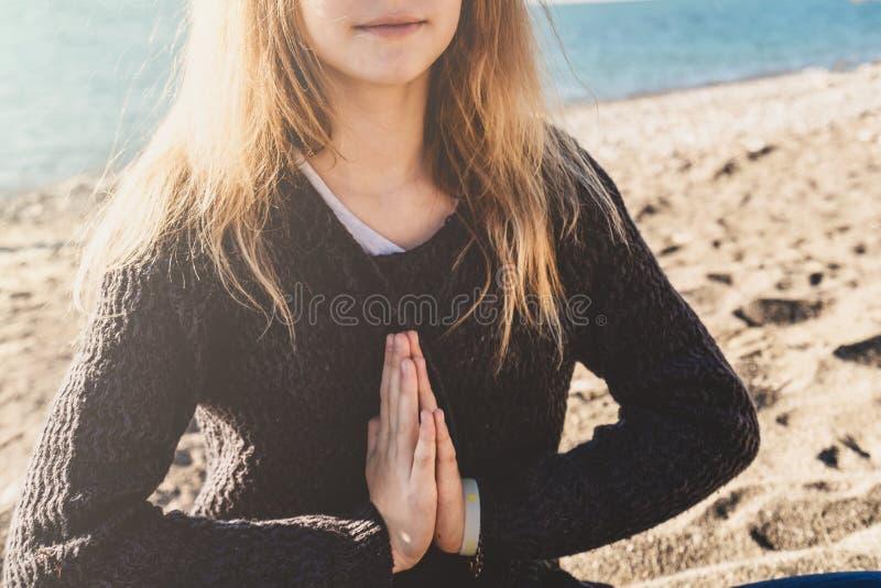 Den lyckliga avkopplade unga kvinnan som mediterar i en yoga, poserar på stranden royaltyfri foto