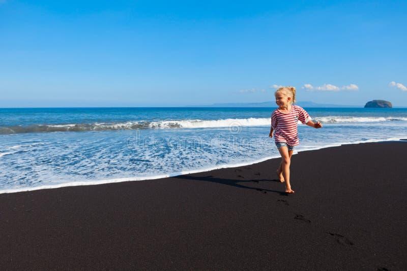 Den lyckliga barfota ungen har gyckel går på vid den svarta stranden arkivfoto