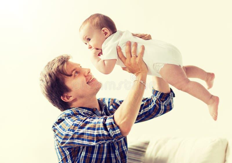 Den lyckliga barnfadern som spelar med, behandla som ett barn hemma royaltyfria foton