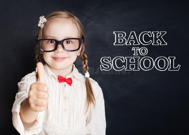 Den lyckliga barnflickan i exponeringsglas med tummen går upp till skolan royaltyfria foton