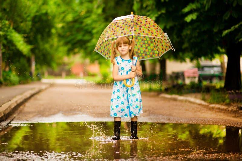 Den lyckliga barnflickan med ett paraply och gummistöveler i pöl på sommar går arkivbild