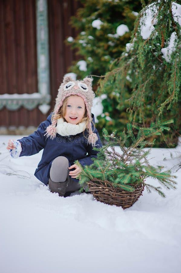 Den lyckliga barnflickan spelar i snöig trädgård för vinter arkivfoto