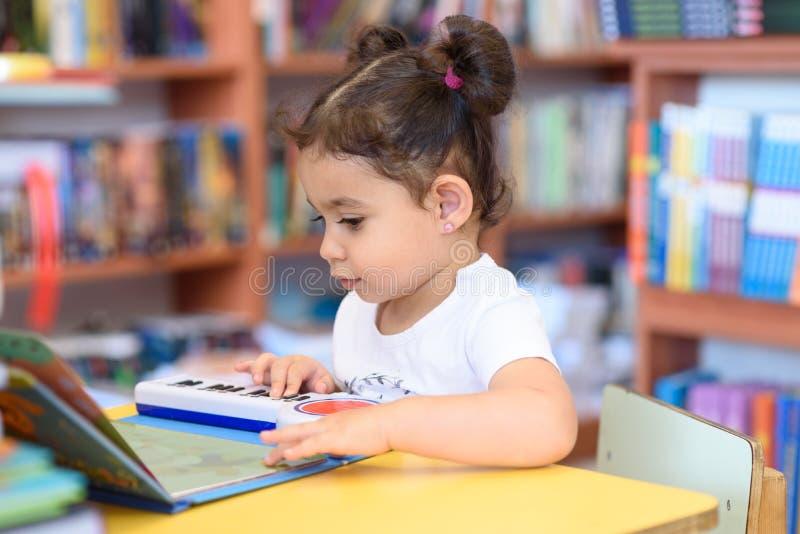 Den lyckliga barnliten flickapianisten spelar p? ett leksakpiano royaltyfri fotografi