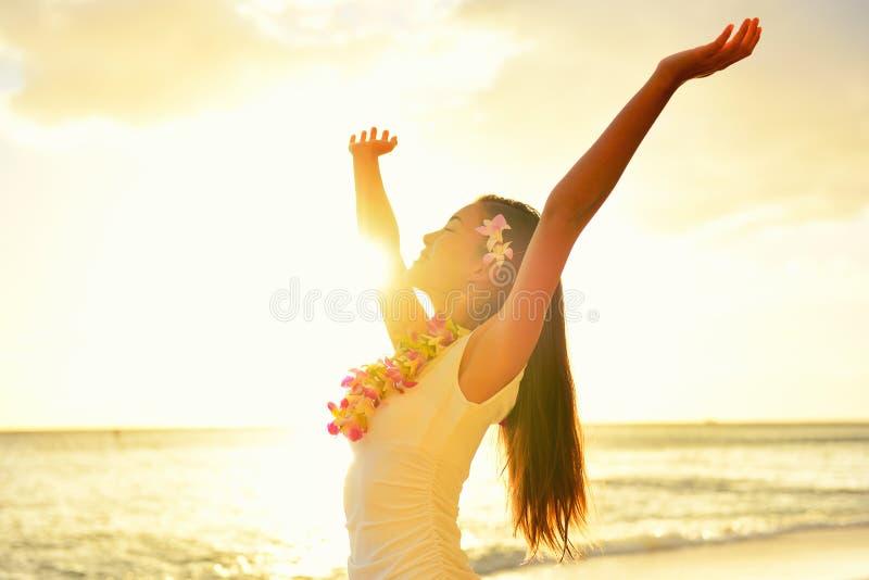 Den lyckliga bekymmerslösa kvinnan frigör i Hawaii strandsolnedgång royaltyfri foto