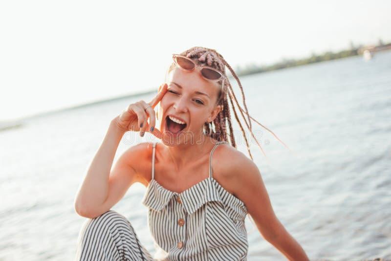 Den lyckliga bekymmerslösa unga kvinnan med afrikanska flätade trådar i solglasögon tycker om liv på stranden, sommarsemestertid royaltyfria bilder