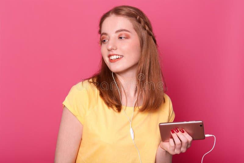 Den lyckliga bekymmerslösa unga kvinnan tycker om av att lyssna till musik från smartphonen, har hörluren, bär den tillfälliga gu royaltyfri foto